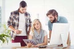 Бизнесмены используя цифровую таблетку пока сидящ на столе Стоковые Фото