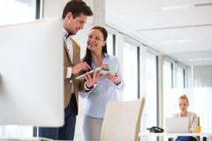 Бизнесмены используя цифровую таблетку с женским коллегой в предпосылке на офисе Стоковое Фото