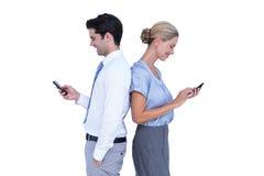Бизнесмены используя smartphone спина к спине Стоковая Фотография