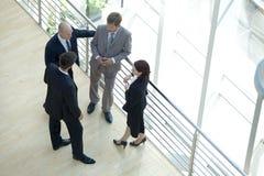 Бизнесмены и женщина стоя совместно путем прокладывая рельсы беседовать Стоковые Изображения RF