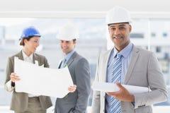 Бизнесмены и женщина с защитными шлемами и светокопией держать Стоковые Изображения RF