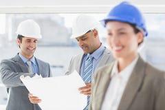 Бизнесмены и женщина с защитными шлемами и светокопией держать Стоковые Изображения