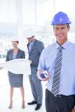 Бизнесмены и женщина с защитными шлемами и светокопией держать Стоковое фото RF