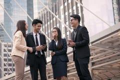 Бизнесмены и женщины собирают счастливое для использования умного телефона и современный Стоковое Изображение