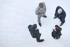 Бизнесмены и коммерсантка стоя совместно и беседуя Стоковая Фотография RF