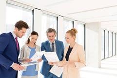 Бизнесмены и коммерсантки обсуждая над документами в новом офисе Стоковое Изображение