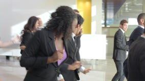 Бизнесмены и коммерсантки танцуя в лобби офиса акции видеоматериалы