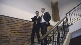 Бизнесмены идут вниз с лестниц и обсуждают проект акции видеоматериалы