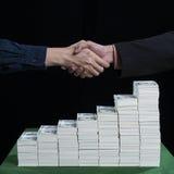 Бизнесмены идя трясти руки против штабелированный долларов Стоковое фото RF