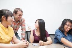 Бизнесмены команды обсуждая азиата человека говоря Стоковые Изображения RF