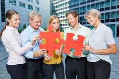 Бизнесмены команды разрешая мозаику Стоковая Фотография