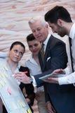 Бизнесмены метода мозгового штурма группы и примечаний принимать к flipboar Стоковая Фотография RF