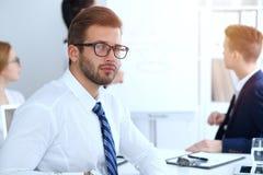 Бизнесмены на встрече в офисе Сфокусируйте на жизнерадостных усмехаясь стеклах бородатого человека нося Конференция, корпоративно стоковые изображения
