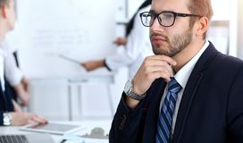 Бизнесмены на встрече в офисе Сфокусируйте на жизнерадостных усмехаясь стеклах бородатого человека нося Конференция, корпоративно стоковое изображение rf