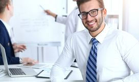 Бизнесмены на встрече в офисе Сфокусируйте на жизнерадостных усмехаясь стеклах бородатого человека нося Конференция, корпоративно стоковое фото rf