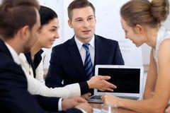 Бизнесмены на встрече в офисе Сфокусируйте на женщине указывая в компьтер-книжку Стоковые Изображения