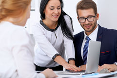 Бизнесмены на встрече в офисе Сфокусируйте на женщине указывая в компьтер-книжку Стоковое Фото