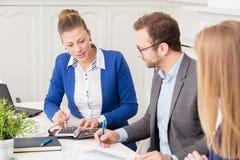 Бизнесмены на встрече сидя на столе конференции Стоковые Фотографии RF