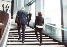 Бизнесмены на зале офисного здания Стоковые Фото