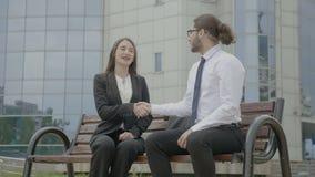 Бизнесмены нося официально костюмы усмехаясь и тряся руки в фронте коммерческая сделка корпоративного здания заключительная сток-видео
