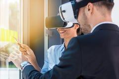 Бизнесмены нося шлемофоны виртуальной реальности пока работающ в офисе Стоковое Изображение RF
