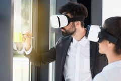 Бизнесмены нося шлемофоны виртуальной реальности пока работающ в офисе Стоковое Изображение