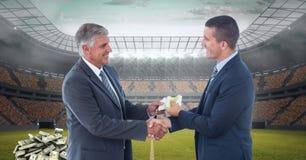 Бизнесмены обменивая деньги представляя коррупцию футбола Стоковая Фотография RF