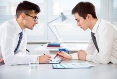 бизнесмены обсуждая детенышей проекта Стоковое Изображение