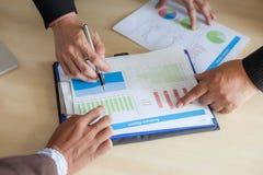 Бизнесмены обсуждая диаграммы и диаграммы стоковые изображения