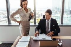Бизнесмены обсуждая документы контракта в офисе Стоковое Изображение