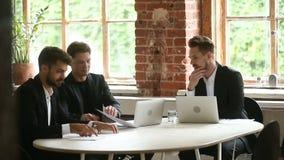 Бизнесмены обсуждая контракт во время переговоров сидя на таблице офиса конференции сток-видео
