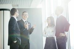Бизнесмены обсуждая на неофициальном заседании в лобби офиса Стоковые Изображения