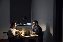 Бизнесмены обсуждая новый проект деятельности на ноче в offic Стоковые Изображения