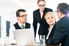Бизнесмены обсуждая план в офисе стоковые изображения