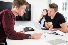 Бизнесмены обсуждая пока коллега используя умный телефон Стоковые Фото