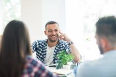 Бизнесмены обсуждая проект на встрече в современном офисе Стоковое Изображение
