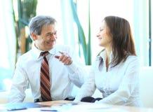 2 бизнесмены обсуждающ, показывающ жестами и усмехающся в офисе Стоковое фото RF