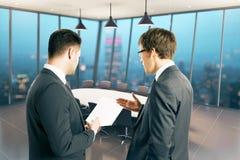 Бизнесмены обсуждая бумагу Стоковые Изображения