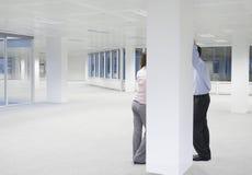 Бизнесмены обсуждая за столбцом нового офиса Стоковые Изображения RF