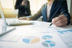 Бизнесмены обсуждая диаграммы и диаграммы показывая res Стоковое фото RF