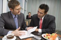 Бизнесмены обсуждая контракт в ресторане Стоковые Фотографии RF