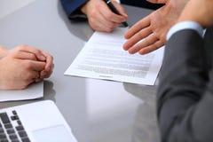 Бизнесмены обсуждая контракт Закройте вверх мужской руки указывая к бумаге Стоковые Изображения RF