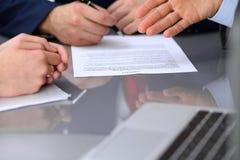 Бизнесмены обсуждая контракт Закройте вверх мужской руки указывая к бумаге Стоковые Фотографии RF