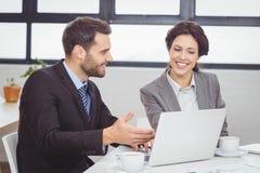 Бизнесмены обсуждая над компьтер-книжкой в конференц-зале Стоковое фото RF