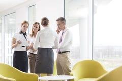 Бизнесмены обсуждая над документами в лобби офиса Стоковая Фотография