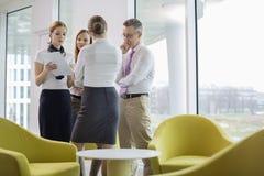 Бизнесмены обсуждая над документами в лобби Стоковое Изображение