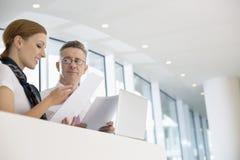Бизнесмены обсуждая над документами в офисе Стоковая Фотография