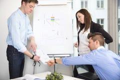 Бизнесмены обсуждая над документом в офисе Стоковые Фото