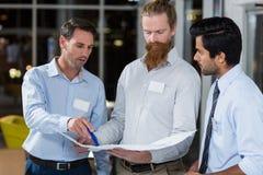 Бизнесмены обсуждая над светокопией Стоковая Фотография RF