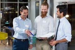 Бизнесмены обсуждая над светокопией Стоковое Изображение